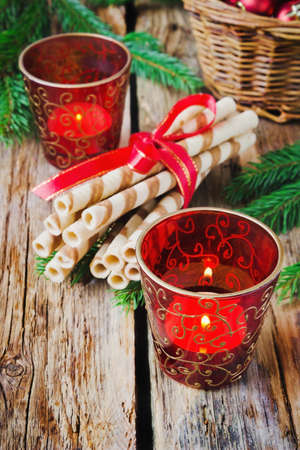 christmas candles in the beautiful christmas glasses  and cookies on the old wooden background. photo