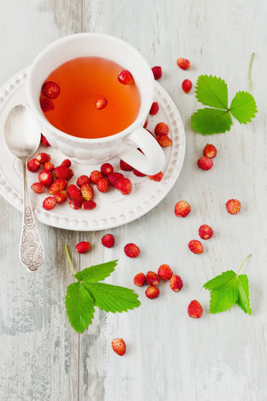 cup of strawberry tea and fresh strawberries on a wooden table. health and diet food photo