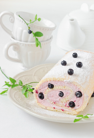 antique dishes: celebratory cake with blueberries and beautiful antique dishes for tea on a white table.