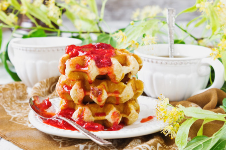 freshly baked waffles with strawberry jam and linden tea. sweet breakfast photo