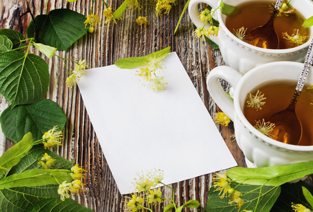 fresh, tasty and healthy linden tea and blank paper for text on a wooden background.copy space background. health and diet food photo