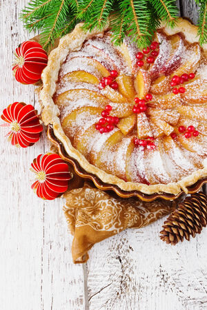 christmas apple pie and christmas decorations on festive table. photo