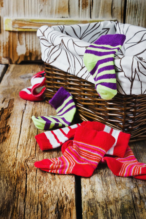 hosiery: scattered childrens striped socks and laundry basket on a wooden background. childrens clothing. Stock Photo