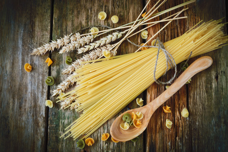 uncooked spaghetti, wheat ears and a wooden spoon on a wooden background.  photo