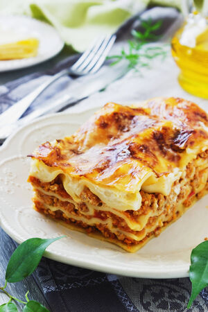 serving freshly cooked lasagna on the dining table. italian cuisine. photo