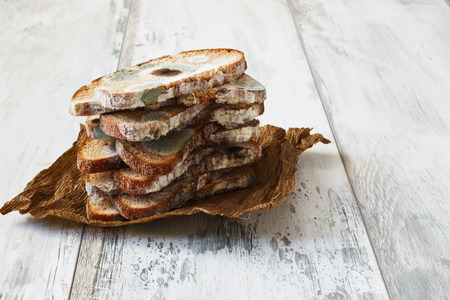 repulsive: spoiled moldy bread on a wooden background. careless attitude toward food Stock Photo
