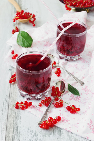 fresh red currant drink with pulp and fresh berries on the wooden background. summer fresh drink. health and diet food photo