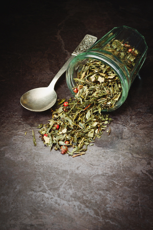 dried tea from different herbs in a glass on a dark background. health and diet food photo