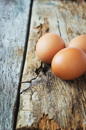 fresh brown chicken eggs on old wooden background. easter symbols photo