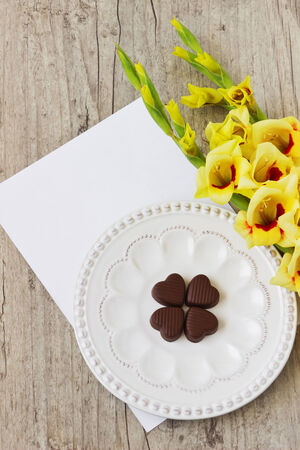 hoja en blanco: ramo de gladiolos amarillos, corazones de chocolate y una hoja de papel en blanco para su inscripci�n en el fondo de madera.