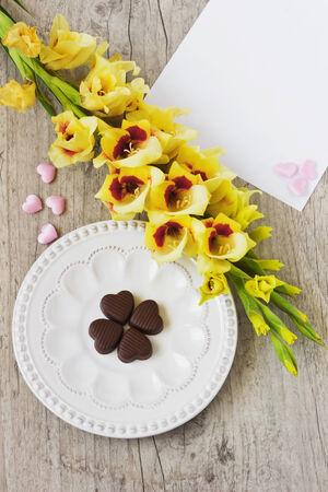 blank sheet: coraz�n de chocolate en un plato, gladiolos amarillos y una hoja de papel en blanco para su inscripci�n en el fondo de madera. la idea de una tarjeta de felicitaci�n. festivales y el fondo del espacio events.copy