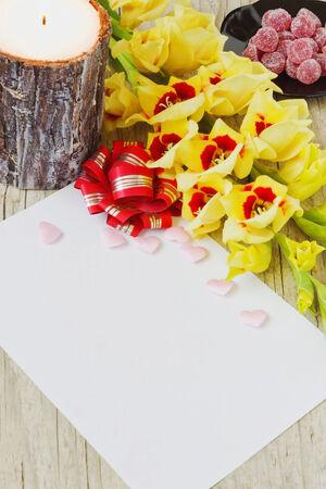 hoja en blanco: hoja de papel en blanco, gladiolo amarillo, vela grande y dulces en un fondo de madera.