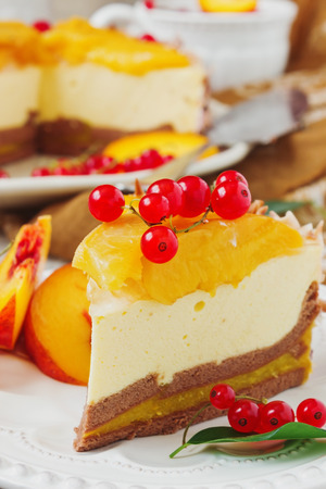 piece of peach cake with red currant berries in a plate on the festive table close up. photo