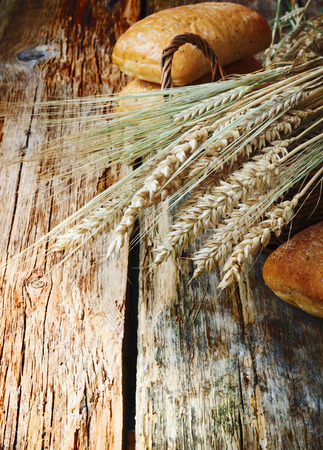 ears of wheat in a basket and freshly baked bread on old wooden background. selective focus photo