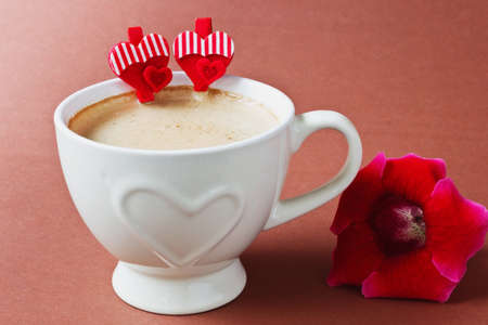 cup of coffee, flower and decorative valentine on a brown background. valentines day. holidays and events photo