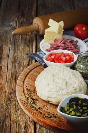 cooked dough and ingredients for pizza on the old wooden table.  retro style photo