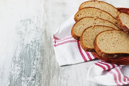 objec: sliced rye bread in a basket on a light wooden background. health and diet food. copy space for you text