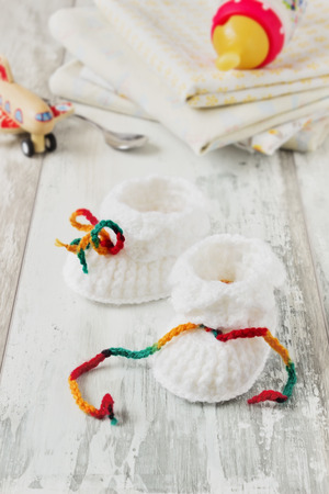 white knitted baby booties and accessories for child care on a wooden background. care for child's health concept. selective focus Banque d'images