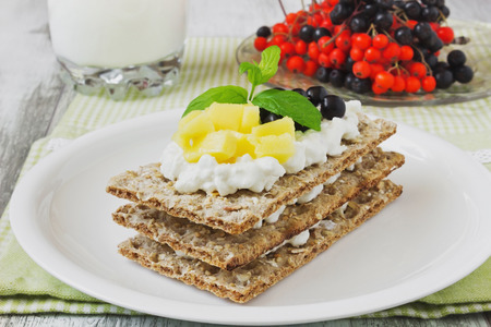 rye bread with cottage cheese ,mango and berries of mountain ash on a white wooden background. healthy breakfast. selective focus. health and diet food photo