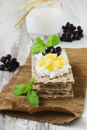 rye bread with cottage cheese mango and berries of mountain ash on a white wooden background.  selective focus. health and diet food photo