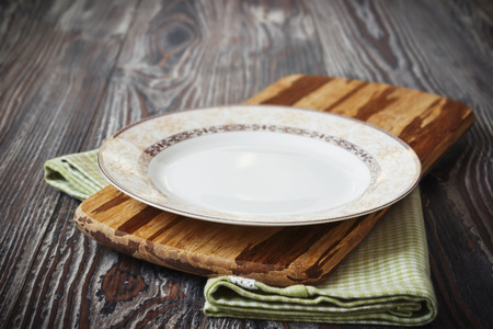 round table: vintage plate on green  kitchen towel on wooden background. kitchen utensils Stock Photo