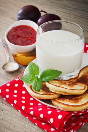 freshly baked fritters on a plate, strawberry jam, ripe plum, mint leaves and milk on the table. traditional european cuisine. photo