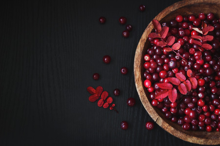 ripe cranberries in a wooden bowl on a black wooden background. health and diet food. copy space background