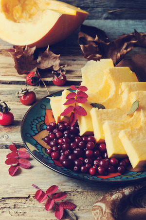 cranberries and sliced pumpkin in a plate on old wooden table, vintage style. autumn motifs.health and diet food photo