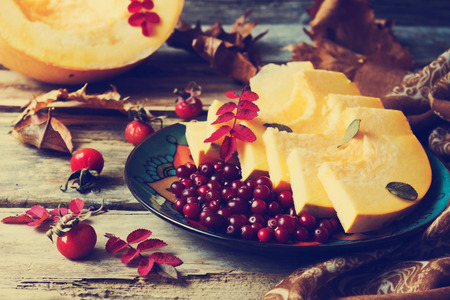 ripe cranberries and sliced pumpkin in a plate on old wooden table, vintage style. autumn motifs.health and diet food.selective focus photo