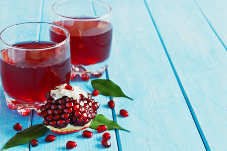 ripe pomegranate seeds and fresh pomegranate juice on a blue wooden background.health and diet food. copy space background photo