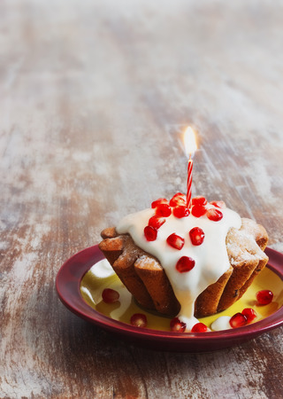 celebratory: celebratory cupcake with cream, pomegranate seeds and a burning candle on a wooden background.selective focus. copy space background