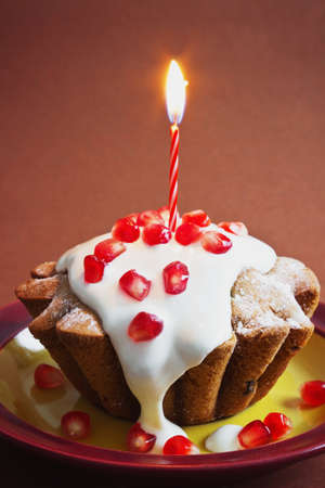 celebratory: celebratory cupcake with cream, pomegranate seeds and a burning candle on a brown background.holidays and events