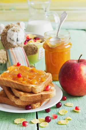 useful for children breakfast of toast with jam, milk and fruits on green wooden table. children food concept photo