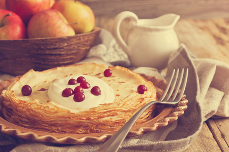 freshly baked pancakes with sour cream and berries in a ceramic dish on the old wooden background. homemade pastries. toned photo in retro style photo