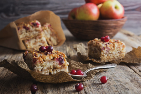 apple tart: slices of cake with cranberries and fresh berries on the old wooden background.rustic style. selective focus Stock Photo