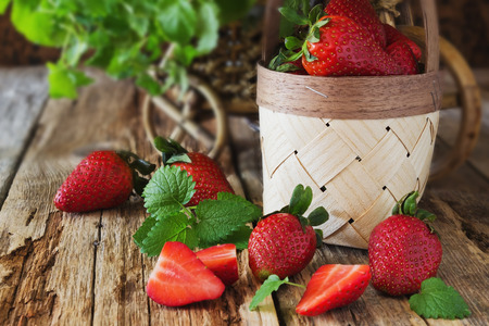 ripe strawberries and mint leaves on a wooden background. berries from his garden.health and diet food. selective focus photo