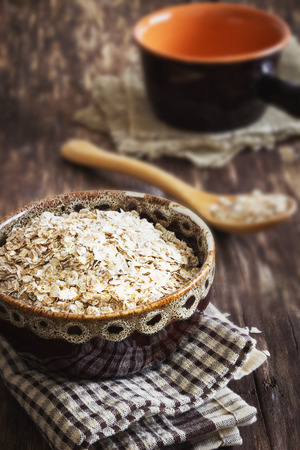 oat flakes in a bowl on the old wooden background. health and diet food. selective focus