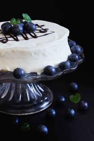 celebratory: celebratory cake with white frosting and fresh blueberries on a dark background. festivals and events.