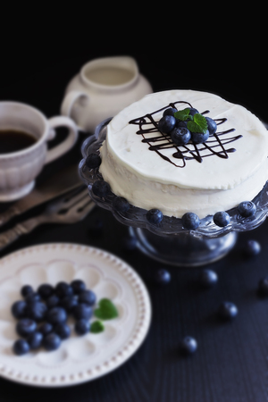 celebratory: celebratory cake with white frosting and fresh blueberries on a dark background. festivals and events. selective focus Stock Photo