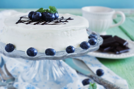 celebratory: celebratory cake with white frosting and fresh blueberries on a wooden background. festivals and events. selective focus Stock Photo