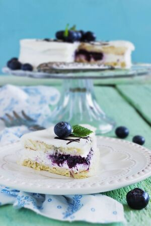 celebratory: celebratory cake with white frosting and fresh blueberries on a wooden table. festivals and events.selective focus