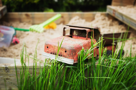 forgotten: old iron toy car forgotten in the grass. kids toys. selective focus Stock Photo