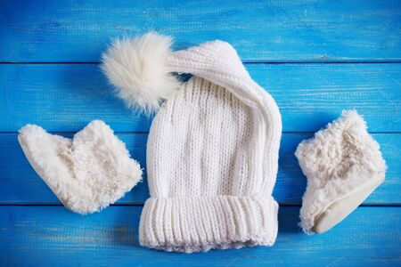 seasonal clothes: winter baby clothes, hat and fur boots on a blue wooden background