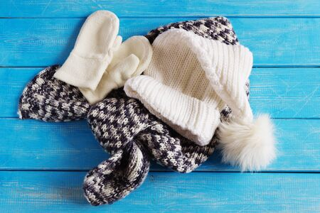 winter baby clothes, hat, scarf and mittens on a blue wooden background. Stock Photo