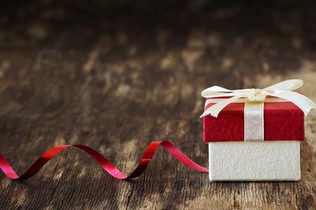古い木製の背景にリボン付きギフト ボックスです。お祭りやイベント。選択と集中。コピー領域の背景 写真素材