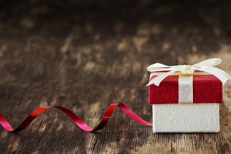 gift background: gift box with a ribbon on the old wooden background. festivals and events. selective focus. copy space background