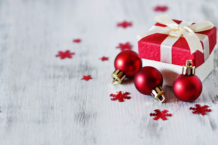 box with christmas gifts and christmas decorations on a white wooden background. selective focus. copy space for you text