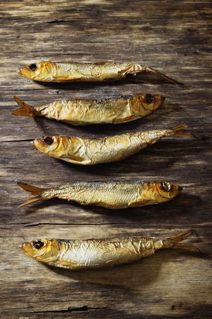 kipper: smoked baltic herring on the old wooden background. rustic style. top view. traditional cuisine. Stock Photo