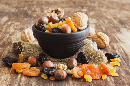 mixed nuts: various dried fruits and nuts on an old wooden background. close-up. judaic holiday tu bishvat. health and diet food. selective focus