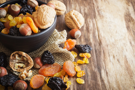 various dried fruits and nuts on an old wooden background. close-up. judaic holiday tu bishvat. health and diet food. copy space background Banco de Imagens